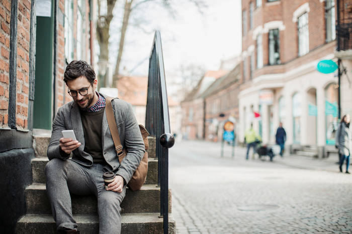 man sitting on stairs with smart phone